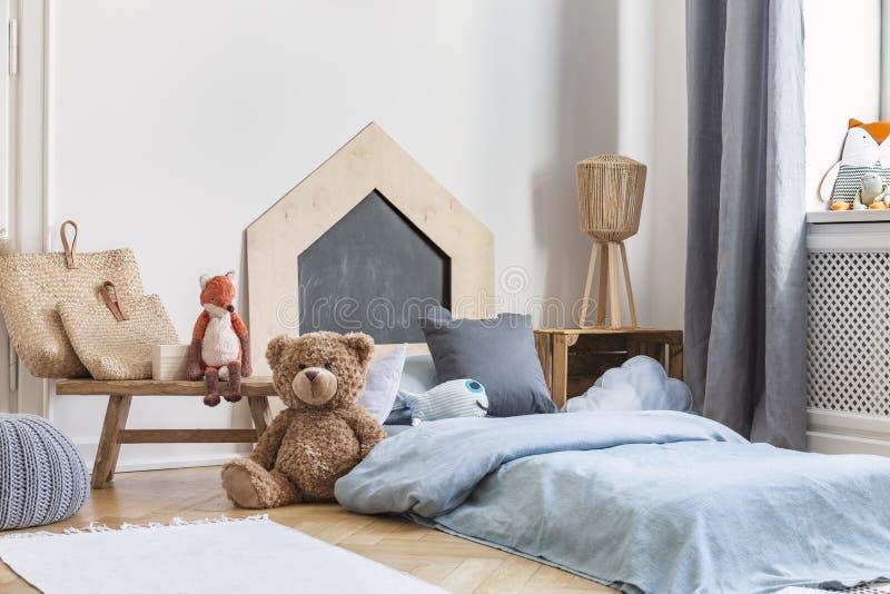 Teddybär nahe bei einem Bett bedeckt mit blauen Blättern in einem natürlichen Kinderrauminnenraum Reales Foto lizenzfreie stockfotos