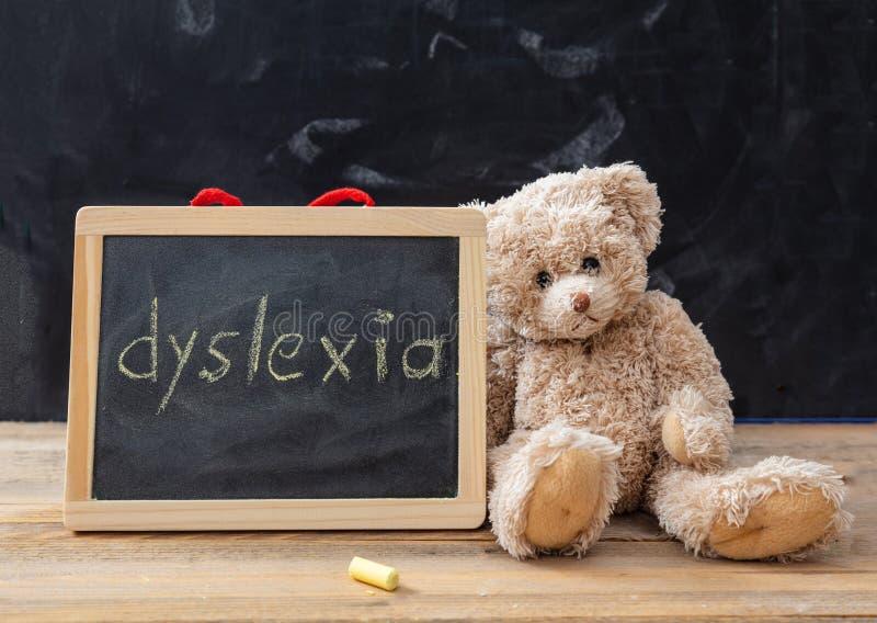 Teddybär und eine Tafel Dyslexietextzeichnung auf der Tafel stockfotografie