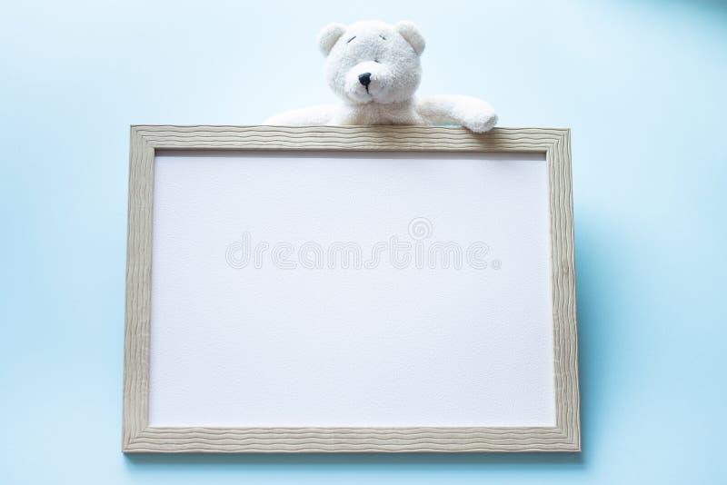 Teddybär und hölzerner Fotorahmen auf blauem Hintergrund Rahmen für Kinder Ein Minimann, der ein Bündel Ballone anhält, steht auf lizenzfreie stockfotos