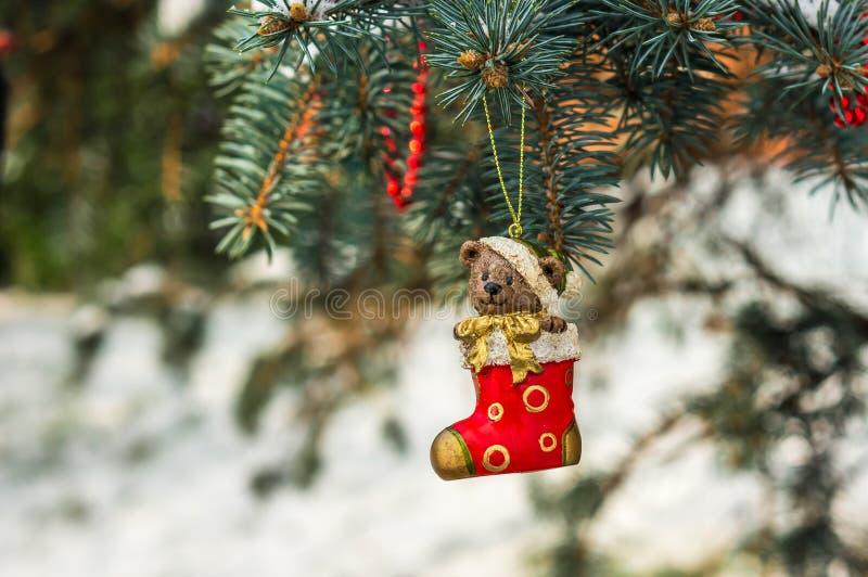 Teddybär und rote Socke, Weihnachtsspielzeug auf einem Weihnachtsbaum stockfotos