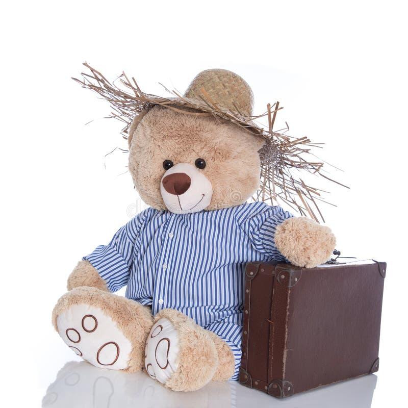 Teddybär weg auf Ferien mit dem Strohhut und Koffer lokalisiert stockbilder