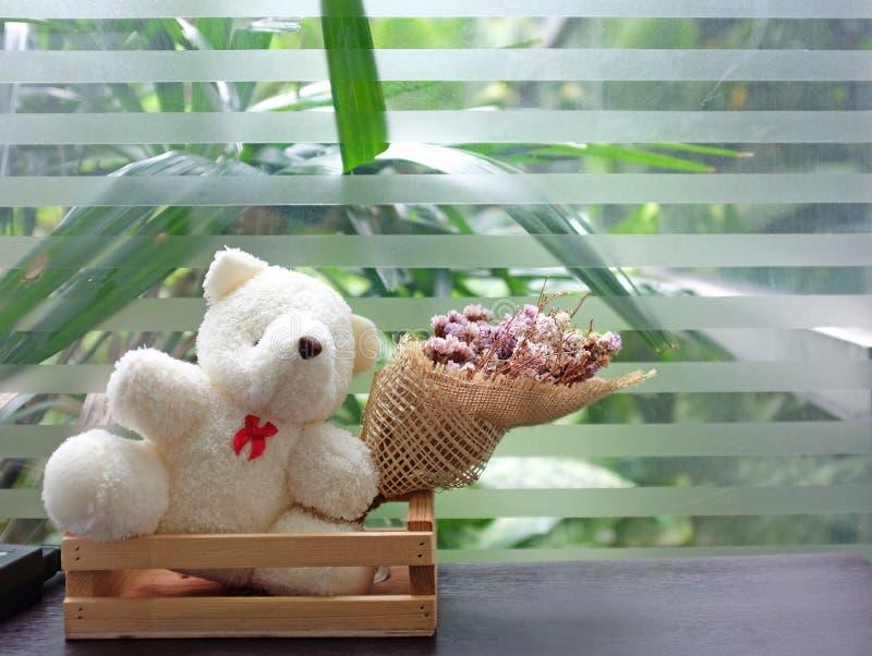 Teddybärpuppe mit Blume des trockenen Grases auf Tabelle nahe Glasfenstern stockbild