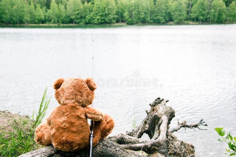 TEDDYB?R-FISCHER Brown-Teddybär sitzt durch den See mit einer Angelrute und fängt Fische stockfoto