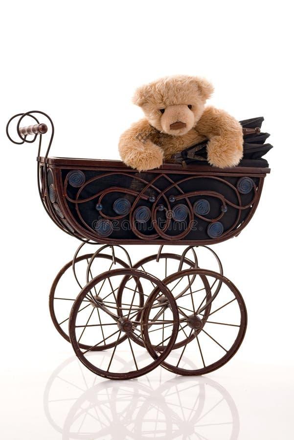 Teddybeer in de retro kinderwagen stock afbeelding