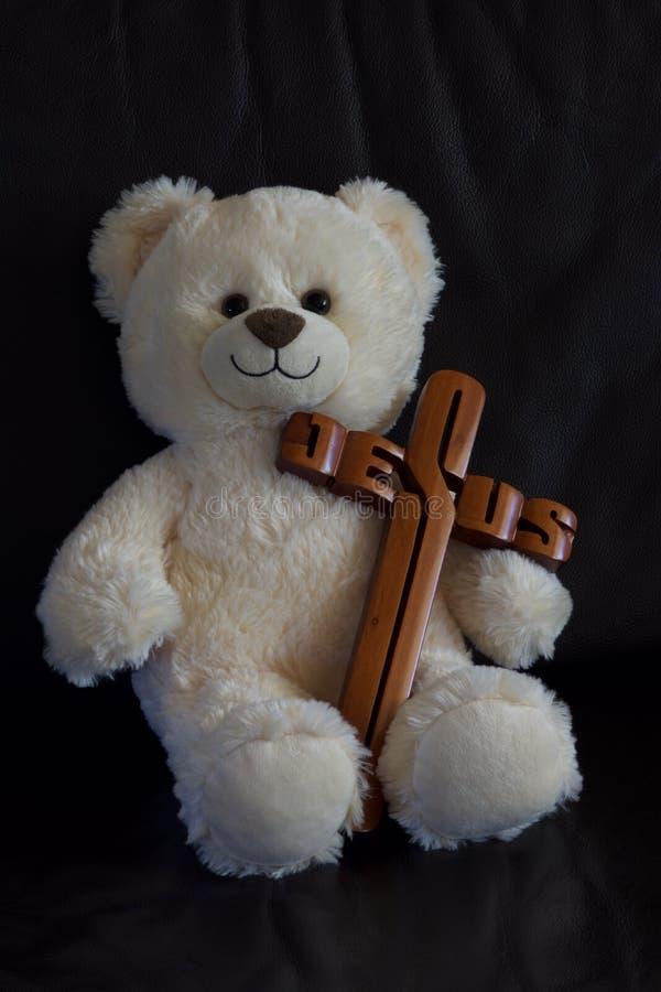 Teddybeer die een kruis dragen stock afbeelding