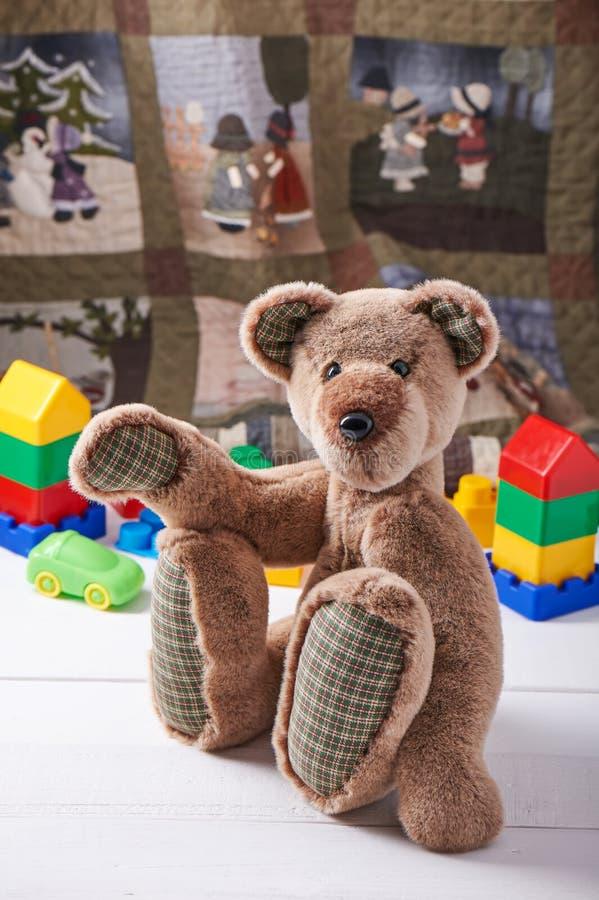 Teddybeer door blokken van plastic de bouwuitrusting die van kinderen wordt omringd royalty-vrije stock afbeelding
