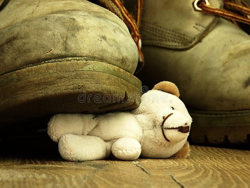 Teddybeer door een zware, oude militaire laars wordt verpletterd die royalty-vrije stock foto's
