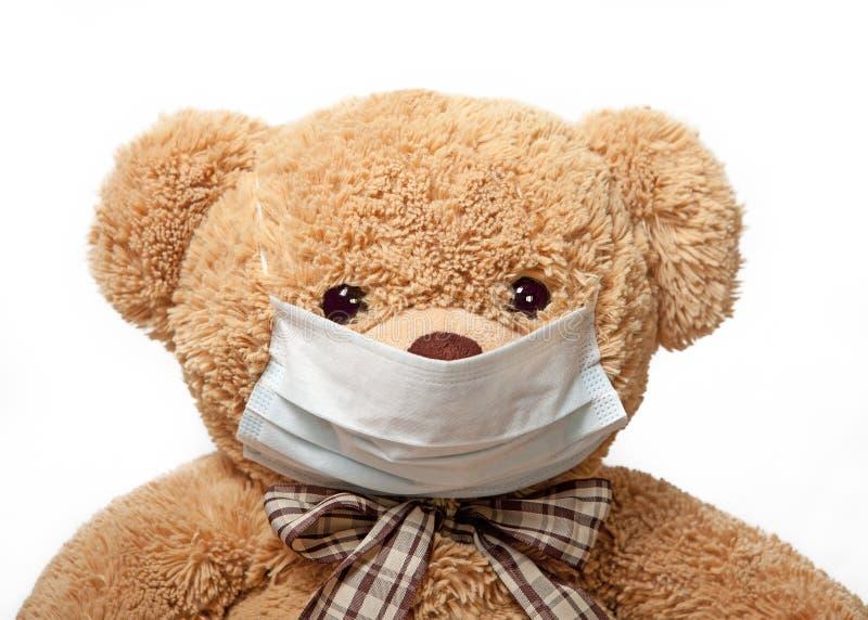 Teddybeer in een medisch masker stock fotografie