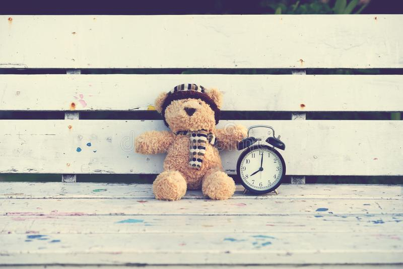 Teddybeer en retro wekker stock fotografie