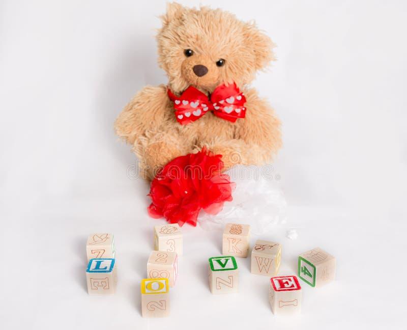 Teddybeer en woord` Liefde ` met jong geitje` s blokken dat wordt gemaakt stock afbeeldingen