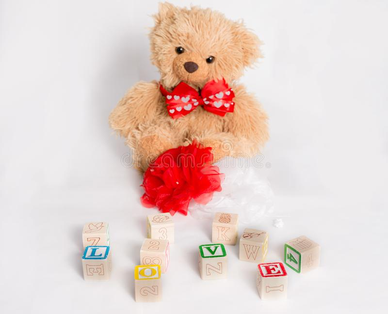 Teddybeer en woord` Liefde ` met jong geitje` s blokken dat wordt gemaakt De voorwerpen zijn op witte achtergrond stock foto's