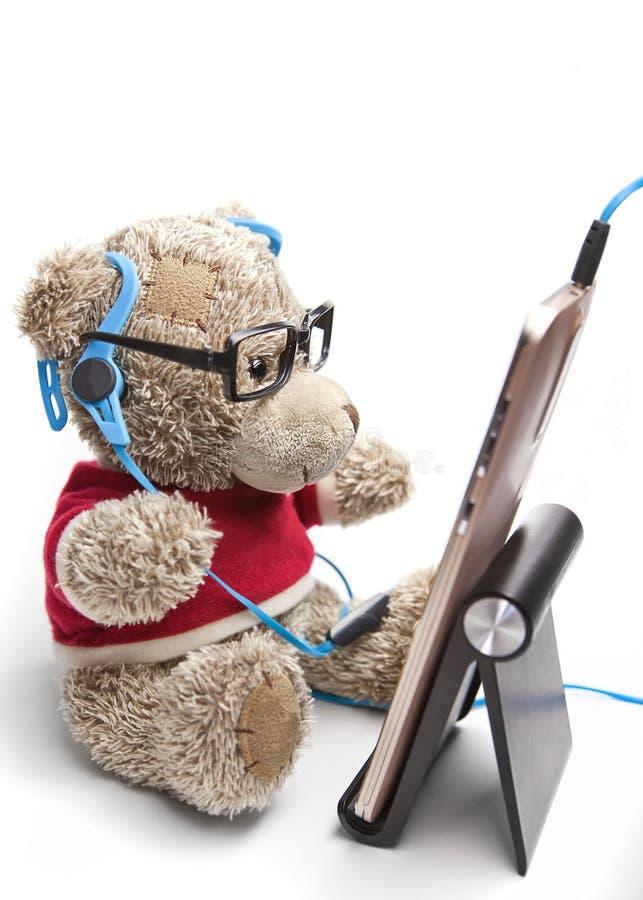 Teddybeer met glazen en hoofdtelefoons zitten die de mobiele telefoon bekijken royalty-vrije stock afbeelding