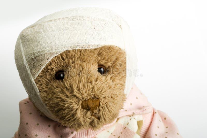 Teddybeer met verband op het hoofd stock afbeelding