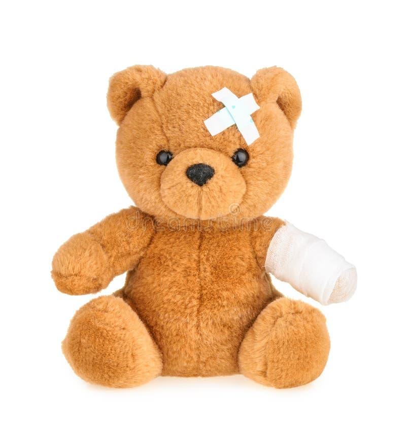 Teddybeer met verband op wit wordt geïsoleerd dat stock afbeeldingen
