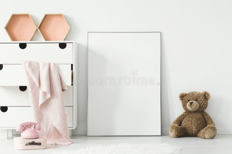 Teddybeer naast witte lege affiche in binnenlandse wi van de baby` s ruimte royalty-vrije stock foto's