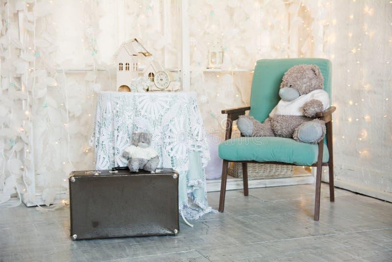 Teddybeer op een oude stoel en een stuk speelgoed huis met klok op de lijst Koffer met een beer op een heldere vakantieachtergron stock afbeeldingen