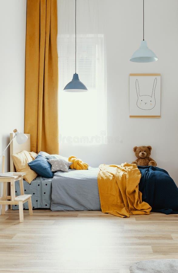 Teddybeer op enig houten bed in blauw en oranje slaapkamerbinnenland stock fotografie