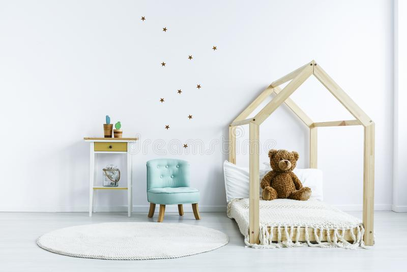 Teddybeer op houten bed naast blauwe stoel in witte jong geitje` s bedro stock foto