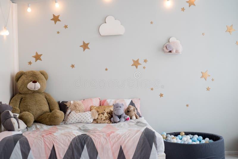 Teddybeer tussen document zakken en houten stoelen in de ruimte van het kind met pastelkleurlamp boven lijst stock foto's