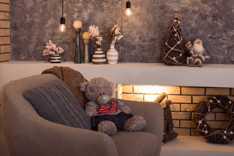 Teddybeerzitting bij de grijze stoel stock foto's