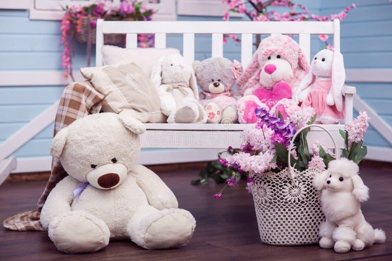 Teddyberen, Konijntje en pluchepoedelzitting op en dichtbij witte houten bank royalty-vrije stock foto