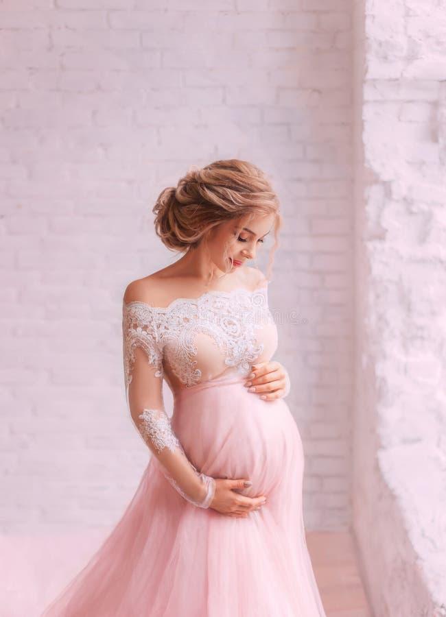 Teder aantrekkelijk jong zwanger meisje die zich alleen in een lichte ruimte bevinden, haar buik bekijken en zacht haar koesteren stock afbeelding