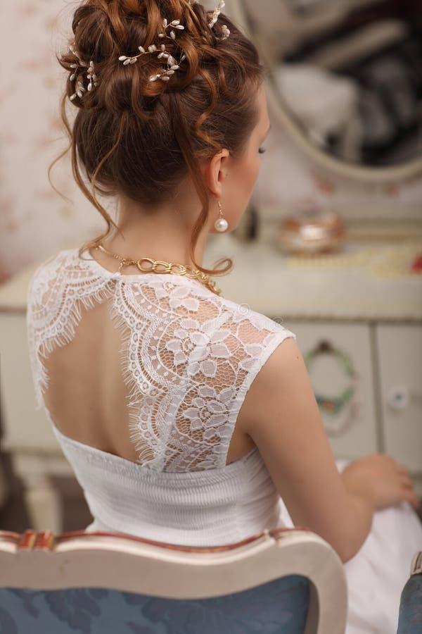 Teder huwelijks modieus kapsel met toebehoren De elegante donkerbruine bruid terug met omhoog verzameld doet haar bruids ochtendp royalty-vrije stock afbeelding
