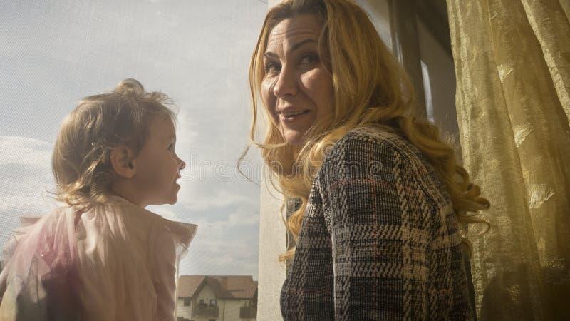 Teder ogenblik tussen moeder en meisjezitting op het venster in het zonsonderganglicht royalty-vrije stock foto's