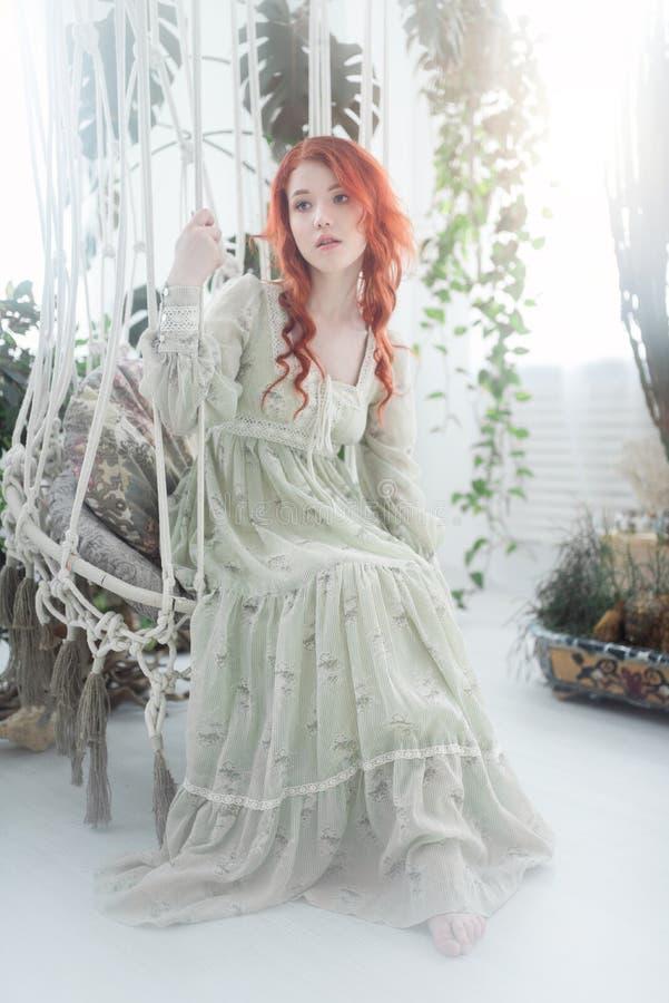 Teder portret van een jonge mooie dromerige roodharigevrouw onder gebladerte in studio stock fotografie