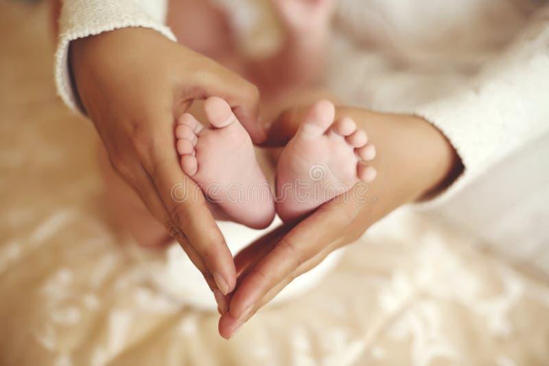 Tedere binnenlandse foto van leuke babyvoeten in mammahanden royalty-vrije stock afbeelding