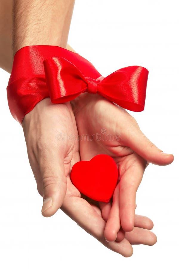 Tedere handen van minnaars met karmozijnrood lint royalty-vrije stock afbeeldingen