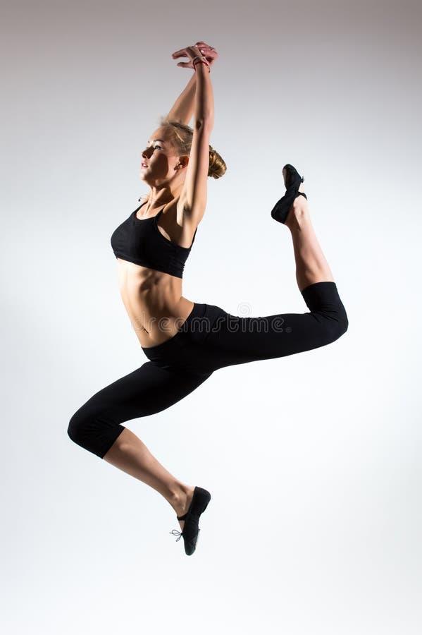 Tederheid, gunst, melodie en plastiek van gymnastiek- meisje Gunstsprong in de lucht van aardig jong meisje stock afbeeldingen
