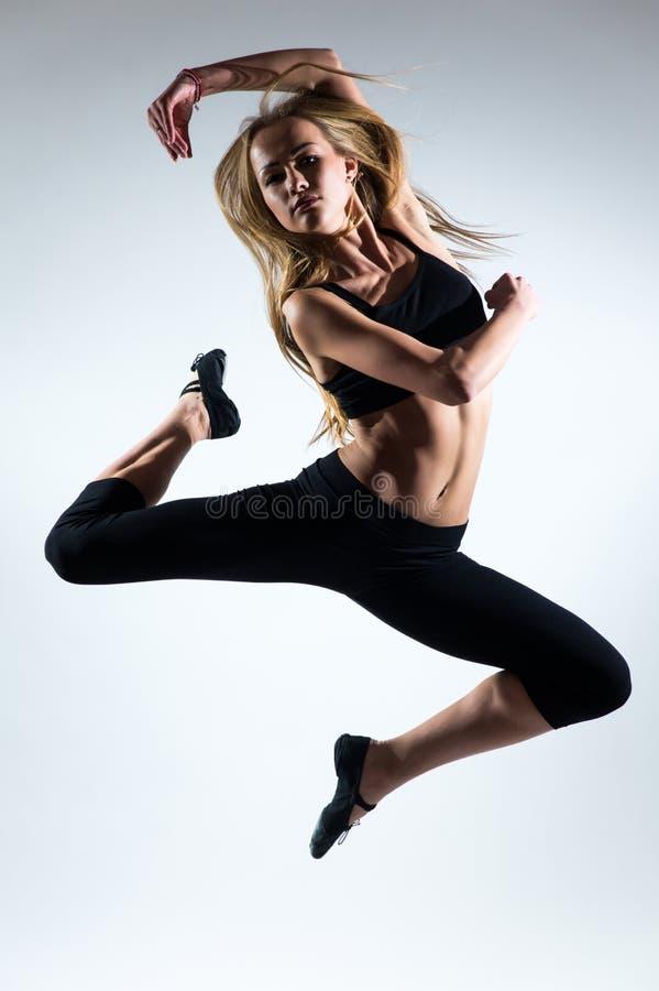 Tederheid, gunst, melodie en plastiek van gymnastiek- meisje Gunstsprong in de lucht van aardig jong meisje stock afbeelding