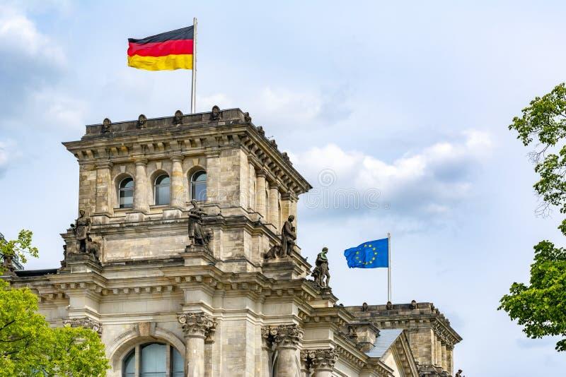 Tedesco e bandiere di UE che si alzano sopra l'edificio Bundestag - Parlamento di Reichstag della Germania a Berlino immagine stock libera da diritti