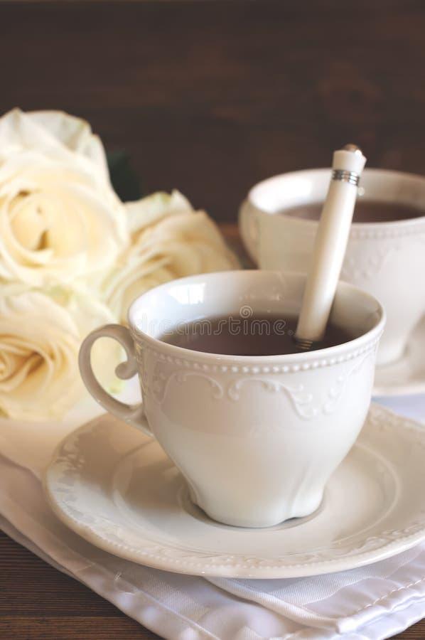 Tee in den Porzellanschalen und -rosen lizenzfreies stockfoto