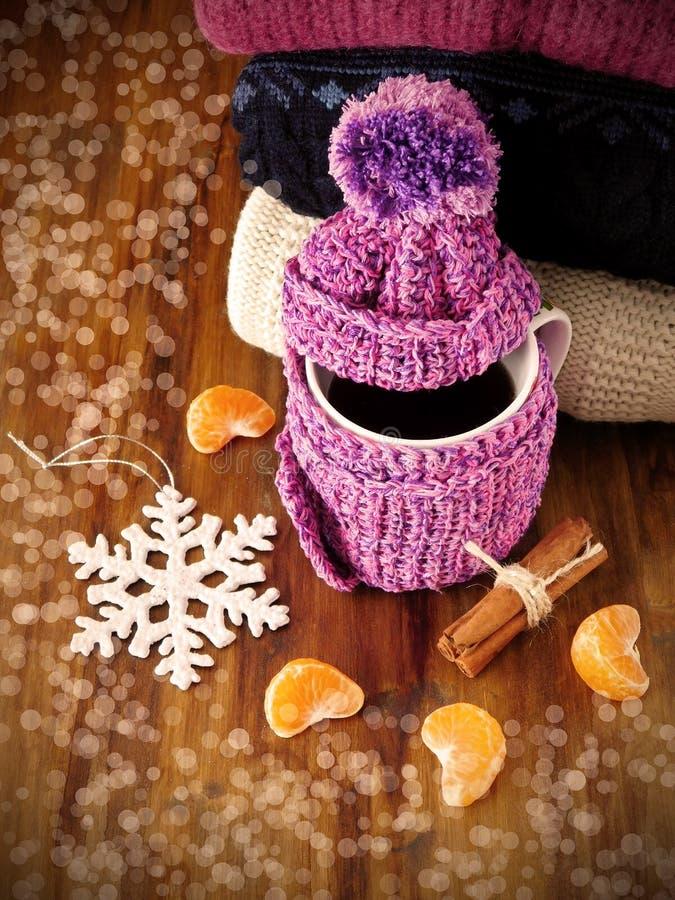 Tee in einem Becher eingewickelt in den kleinen Schal umgeben durch Mandarinensegmente und -Zimtstangen lizenzfreies stockfoto