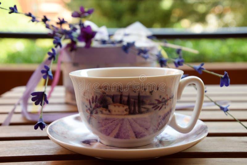 Tee im Garten, weiße Teetasse mit purpurrotem Muster stockbild