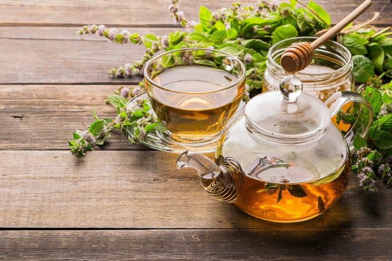 Tee mit frischen Blättern der Melissenminze in einer Schale und in einer Teekanne auf einem hölzernen rustikalen Hintergrund Heil stockfotografie