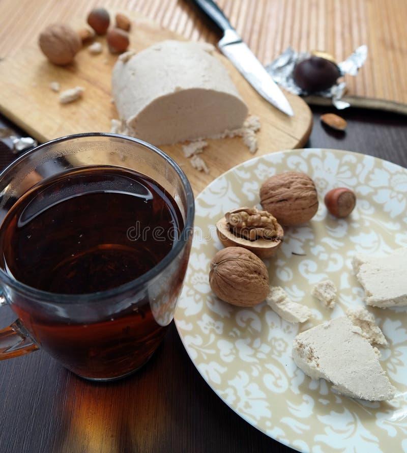 Tee mit halva und Nüsse auf Tabelle lizenzfreie stockbilder