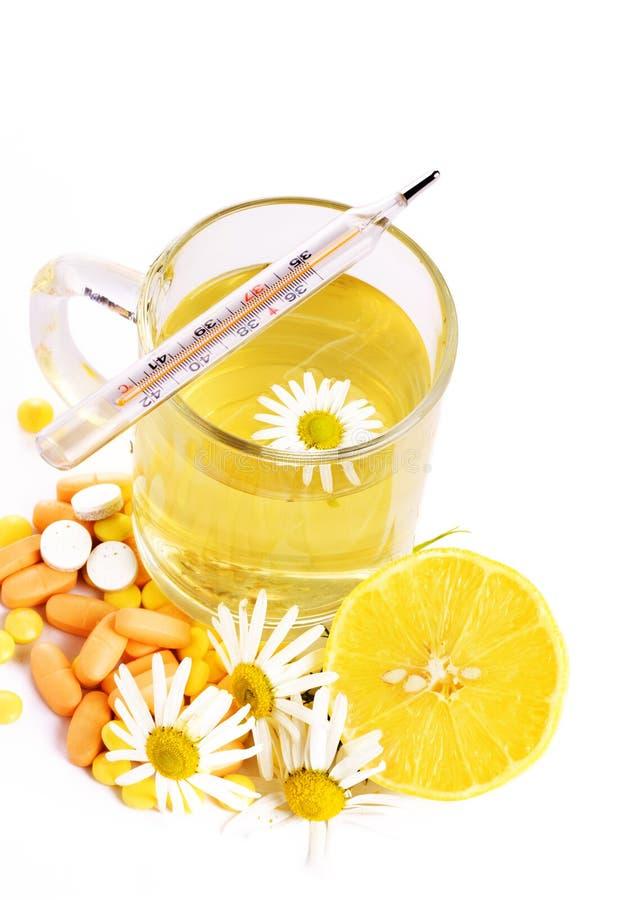 Tee mit Kamille, Zitrone, Thermometer und Pillen lizenzfreies stockfoto