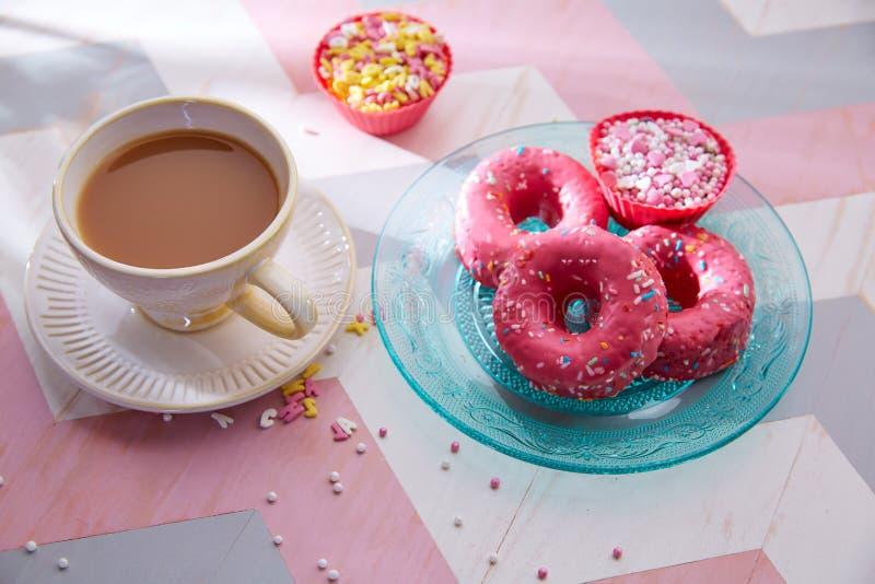 Tee mit Milchfrühstück mit rosa Donas lizenzfreie stockfotografie