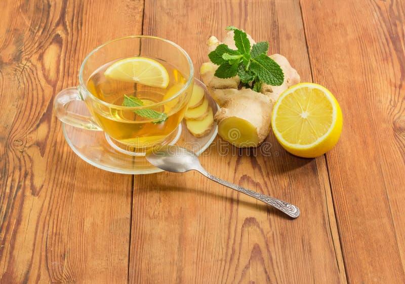 Tee mit Minzen-, Ingwer- und Zitronenscheiben in der Glasschale lizenzfreie stockbilder