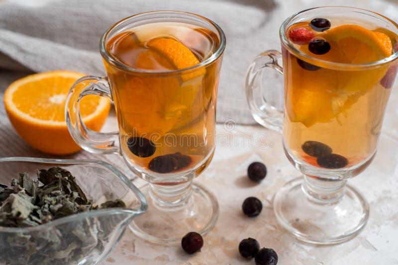 Tee mit Orange Dunkler h?lzerner Hintergrund Ein altes Buch und Lebkuchen im Hintergrund stockbilder