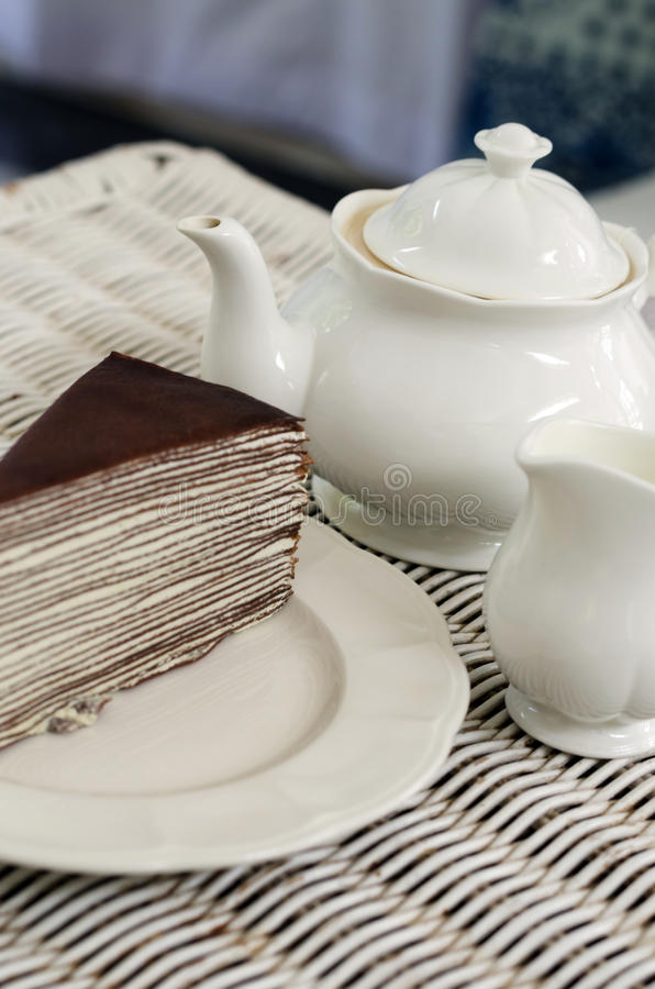 Tee mit Schokoladenkreppkuchen auf Gewebebeschaffenheit lizenzfreie stockfotos