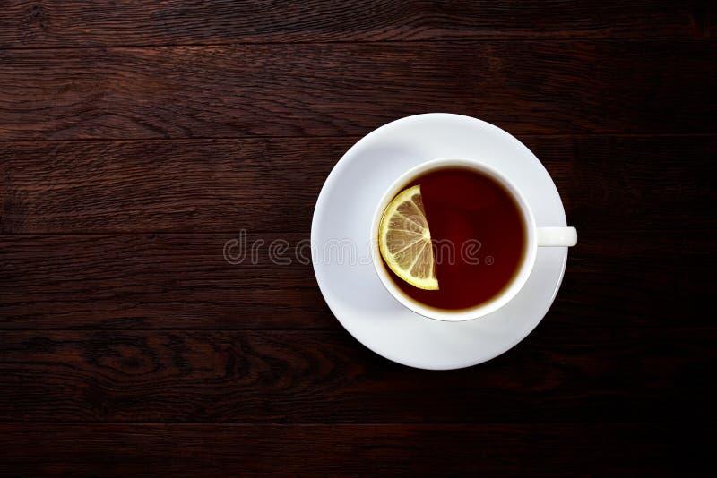 Tee mit Zitrone in der weißen Schale, Zimtstangen, strickte woolen Schal auf Holztisch lizenzfreie stockbilder