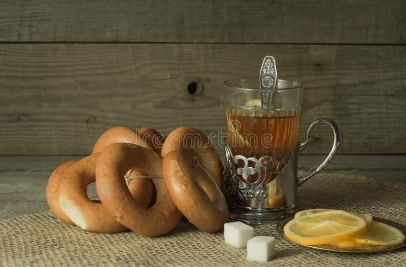 Tee mit Zitrone im Becherhalter auf altem Holztisch lizenzfreies stockfoto