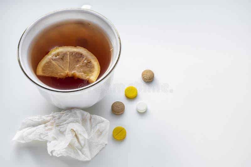 Tee mit Zitrone, Pillen und Taschentuch auf der weißen Tabelle Das Konzept von Kälten lizenzfreies stockbild