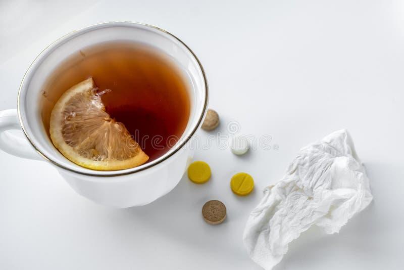 Tee mit Zitrone, Pillen und Taschentuch auf der weißen Tabelle Das Konzept von Kälten lizenzfreie stockfotos