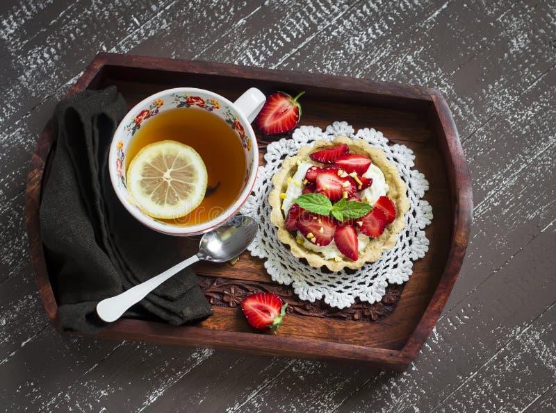 Tee mit Zitrone Tartlet mit Sahne und Erdbeeren in einem Weinlesebehälter lizenzfreie stockbilder