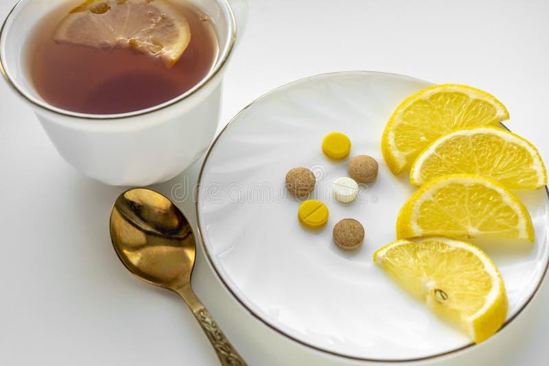 Tee mit Zitrone und Pillen auf der weißen Tabelle Das Konzept von Kälten lizenzfreie stockbilder
